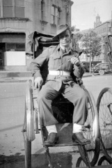 Vince poses in a rickshaw on the street in post WW II Tokyo.