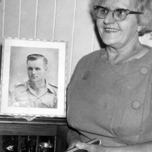 Thelma Healy at home in Miles Street, Wooloowin, Brisbane, holding her travel diary in front of a picture of Vince after her return from Pusan.